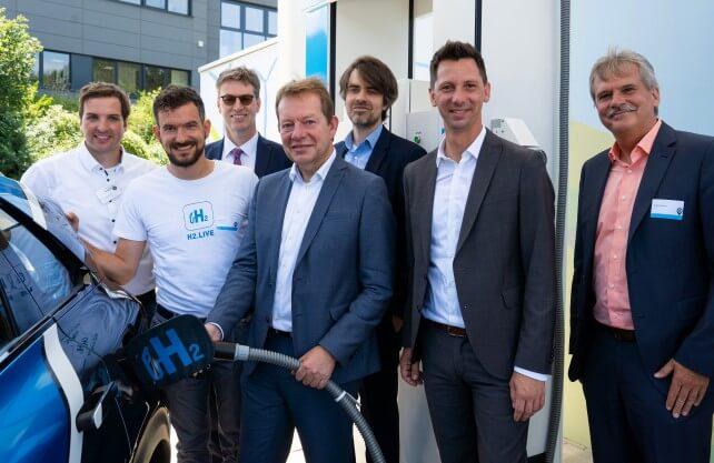 Siegens Bürgermeister Steffen Mues (4.v.l.) und Landrat Andreas Müller (5.v.l.) bei der Übergabe der ersten Wasserstoff-Tankstelle Südwestfalens in Siegen. Foto: H2 Mobility