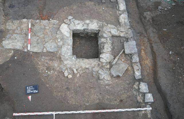 Der quadratische Umriss aus Kalkstein ist die Latrine, darum erkennbar im Boden eine kreisrunde Verfärbung: die Baugrube für die Latrine. Foto: T. Lodemann/EggensteinExca