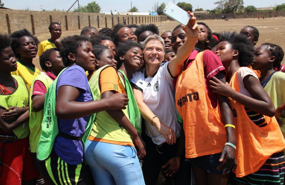 """""""Dort tanke ich auf"""" - Petra Landers im Rahmen inmitten afrikanischer Fußballerinnen. Foto: privat."""